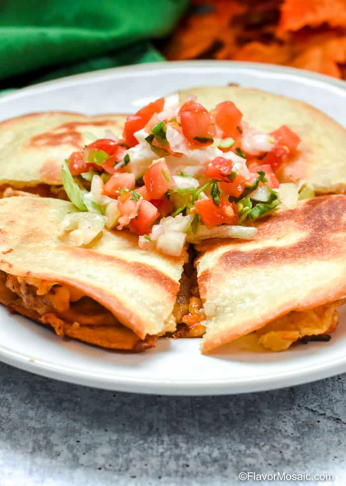 Side view of chicken bacon ranch quesadillas topped with lettuce sour cream and Pico De Gallo