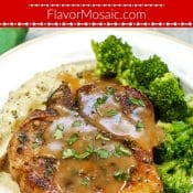 Picture of pork chops covered in gravy served with broccoli and mashed potatoes on white plate.