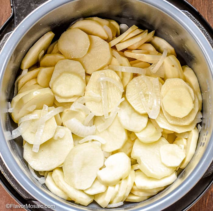 Overhead photo of sliced potatoes and onions in Instant Pot