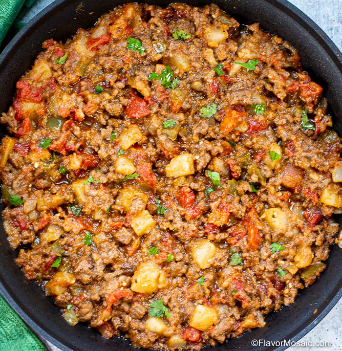 Overhead photo of finished Picadillo Con Papas recipe in black skillet
