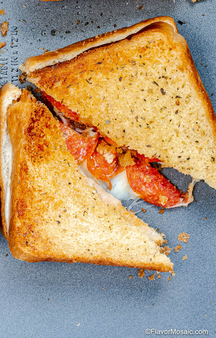 Baked Pizza Grilled Cheese Sandwich sliced in half laying on a sheet pan