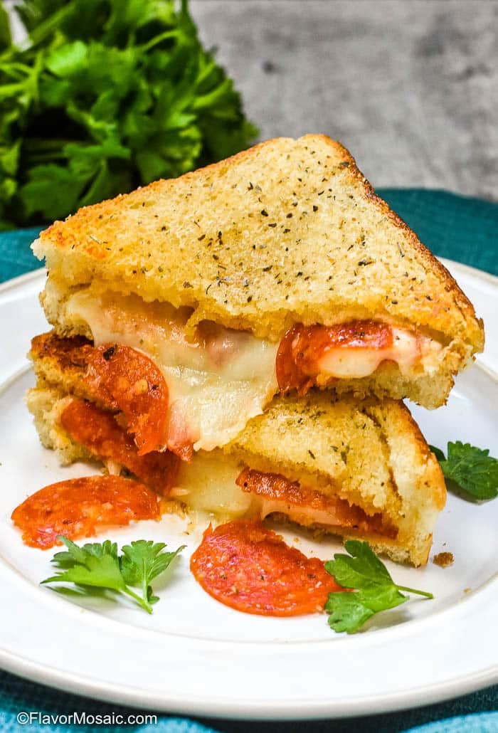 Baked Pizza Grilled Cheese Sandwiches stacked on a white plate