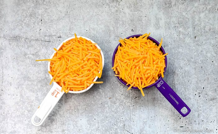 Overhead photo of 2 measuring cups (one white and one purple) filled with shredded sharp cheddar cheese.