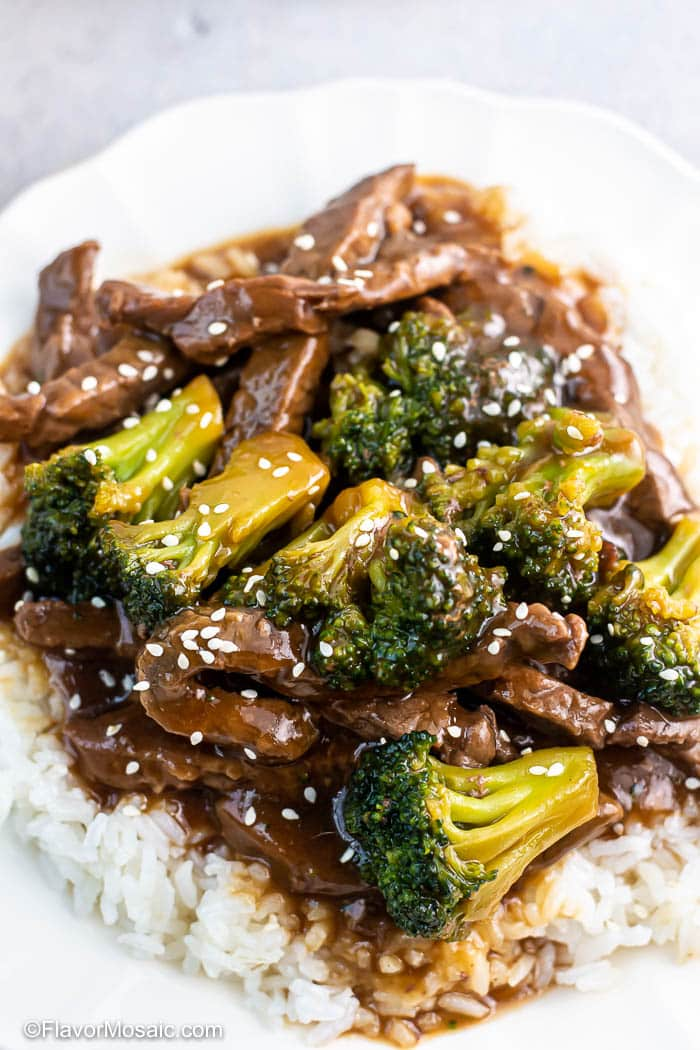 Overhead view of white place with Instant Pot Beef And Broccoli on top of white rice and sprinkled with sesame seeds.