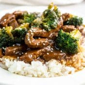White place with a serving of Instant Pot Beef And Broccoli with white rice and sprinkled with sesame seeds.