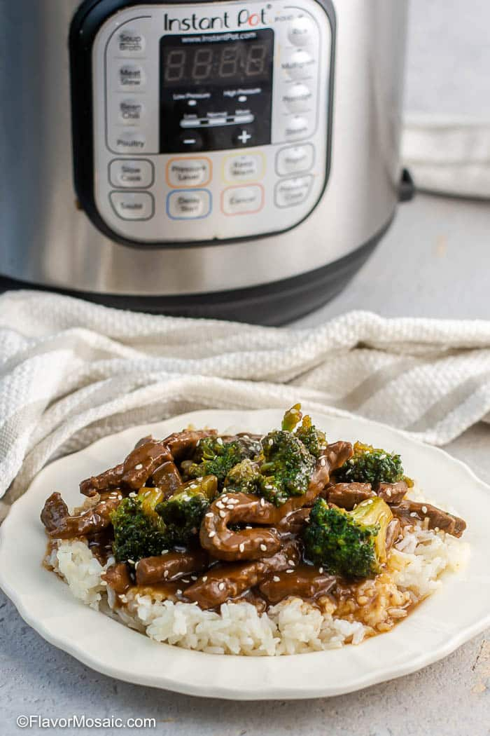 White plate with Instant Pot Beef And Broccoli over white rice and sprinkled with sesame seeds sitting in front of Instant Pot Pressure Cooker and white and beige striped napkin.