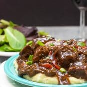 An individual serving of Instant Pot Beef Tips and Gravy served over mashed potatoes on a blue plate sitting on a larger white plate with a salad and glass of wine in the background.