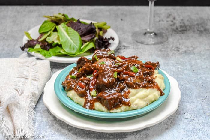 Horizontal photo of serving of Instant Pot Beef Tips And Gravy with salad and glass of wine.