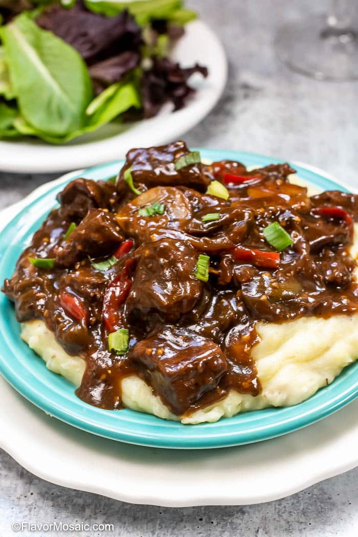 Serving of Instant Pot Beef Tips And Gravy served over mashed potatoes with onions, red and green bell peppers and mushrooms with a salad in the background.