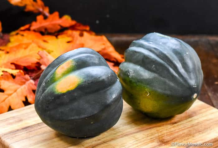 Picture of two whole acorn squashes sitting on a cutting board.