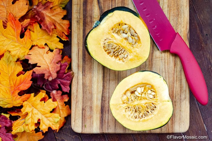 Two halves of one acorn squash sitting on a cutting board with the sliced side facing up with seeds.