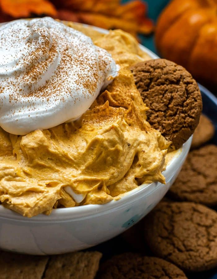 A bowl of Pumpkin Fluff with Cool Whip And Marshmallows and served on a plate with gingerbread snaps.