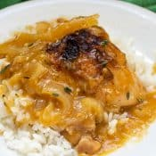 One serving of Cajun Braised Chicken With Gravy over rice on white plate with green napkin in the background.
