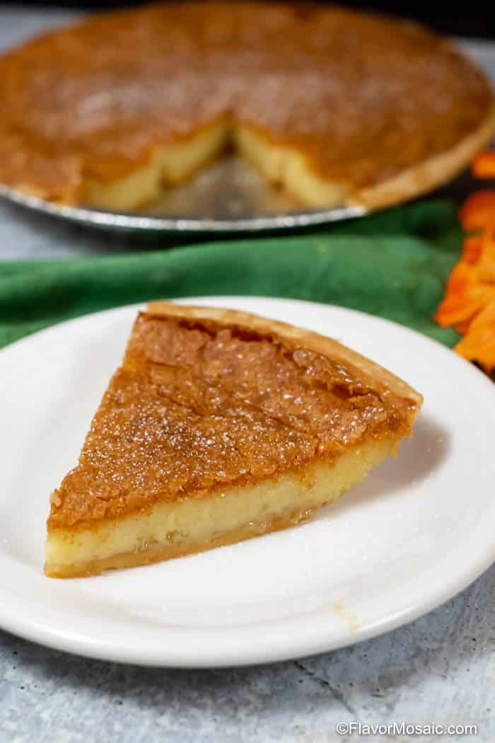 Slice of Chess Pie on White Plate with green napkin and whole pie in the background.