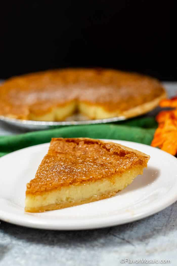 Vertical photo of slice of pie on white plate in front of rest of pie with black background.