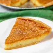 Slice of chess pie on white plate with green napkin and whole pie in background.