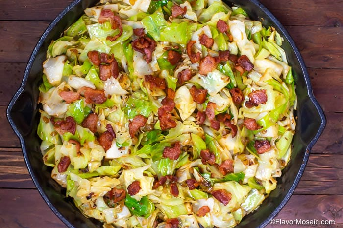 Horizontal overhead photo of Fried Cabbage with Bacon in a cast iron skillet on a wood table.