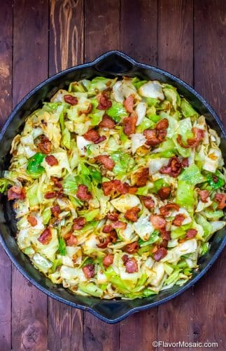 Overhead view of Fried Cabbage with Bacon in Skillet on wood table.