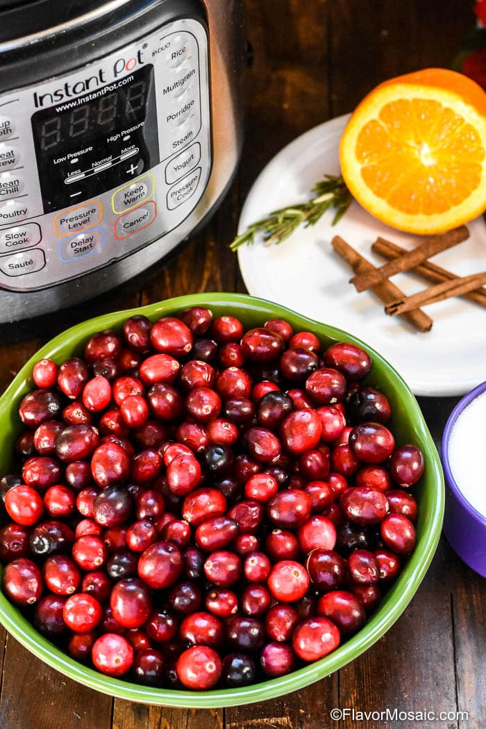 Ingredients for Instant Pot Cranberry Sauce with green bowl of fresh cranberries next to Instant pot next to white plate with sliced orange, cinnamon stings, and twigs of rosemary.