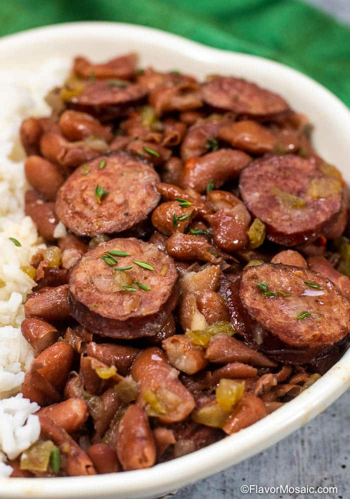 Right half of bowl of red beans and rice with andouille sausage with green napkin in background.
