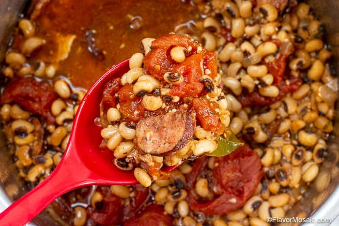 Overhead view of red spoon with black eyed peas with sausage, stewed tomatoes held over the black eyed peas in an Instant Pot.