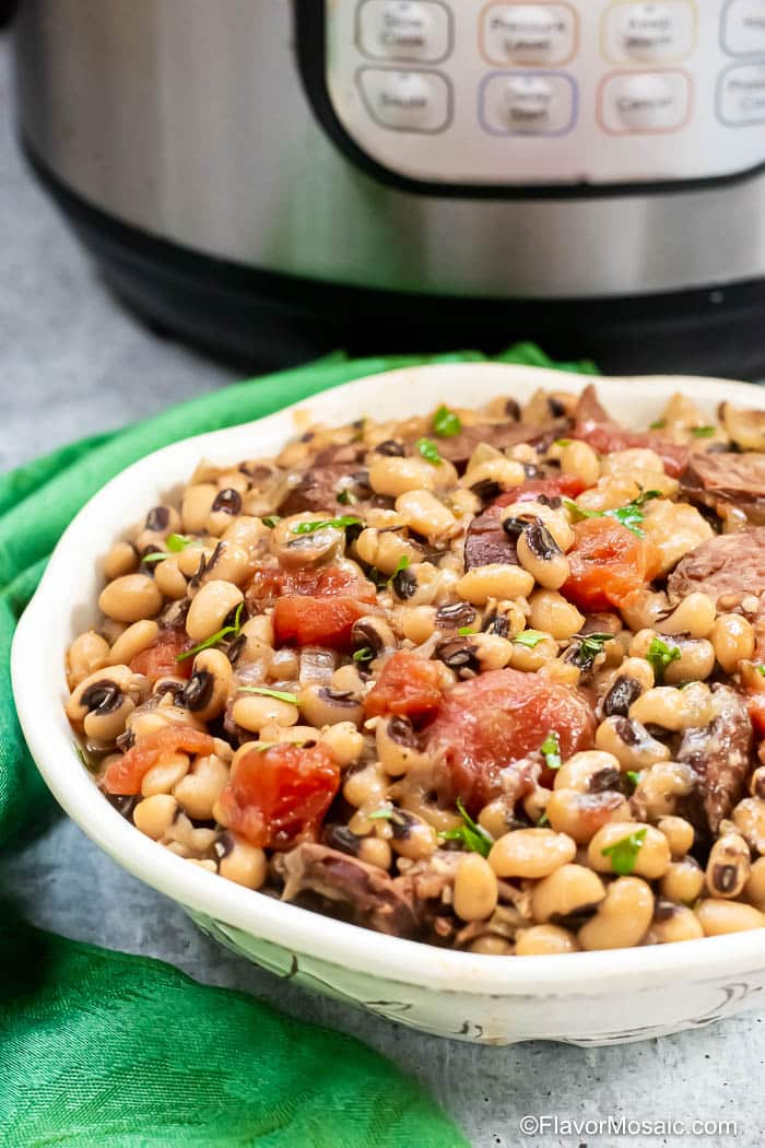 Side view of white bowl with black eyed peas with stewed tomatoes, andouille sausage, bacon, and parsley.