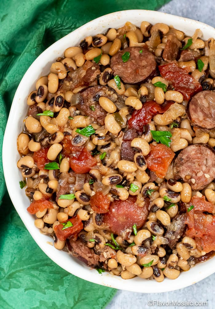 Overhead view of white bowl with Instant Pot Black Eyed Peas with tomatoes, sausage, and bacon.