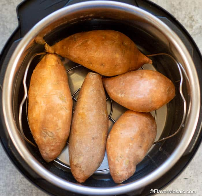 Overhead photo of 5 whole sweet potatoes inside an Instant Pot.