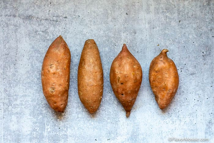 4 sweet potatoes in a row on a gray cement background.