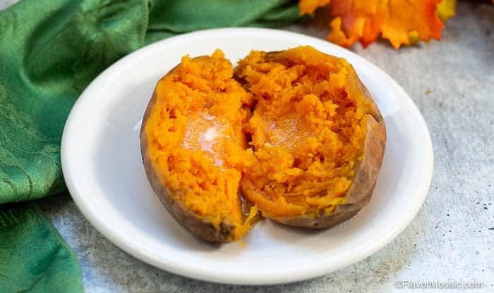 One fully cooked sweet potato, sitting on white plate, cut in half vertically with each half laying flat on the plate with the cut side up with a pat of butter that is partially melted on each half.