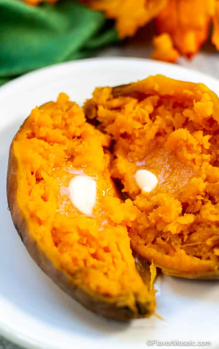 One cooked sweet potato with button on a white plate with a green napkin and fall leaves in the background.