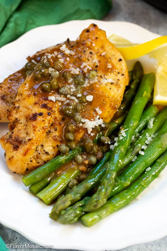 Instant Pot Chicken Piccata on white plate with asparagus and slice of lemon.