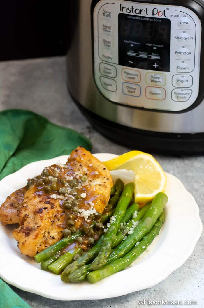 Chicken Piccata on white plate with asparagus and slice of lemon with green napkin on the side and an Instant Pot in the background.