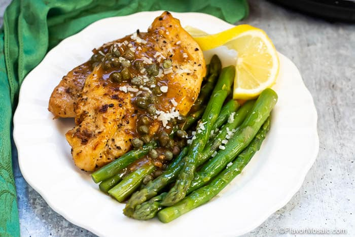Horizontal photo of asparagus on white plate with chicken piccata and lemon slice.