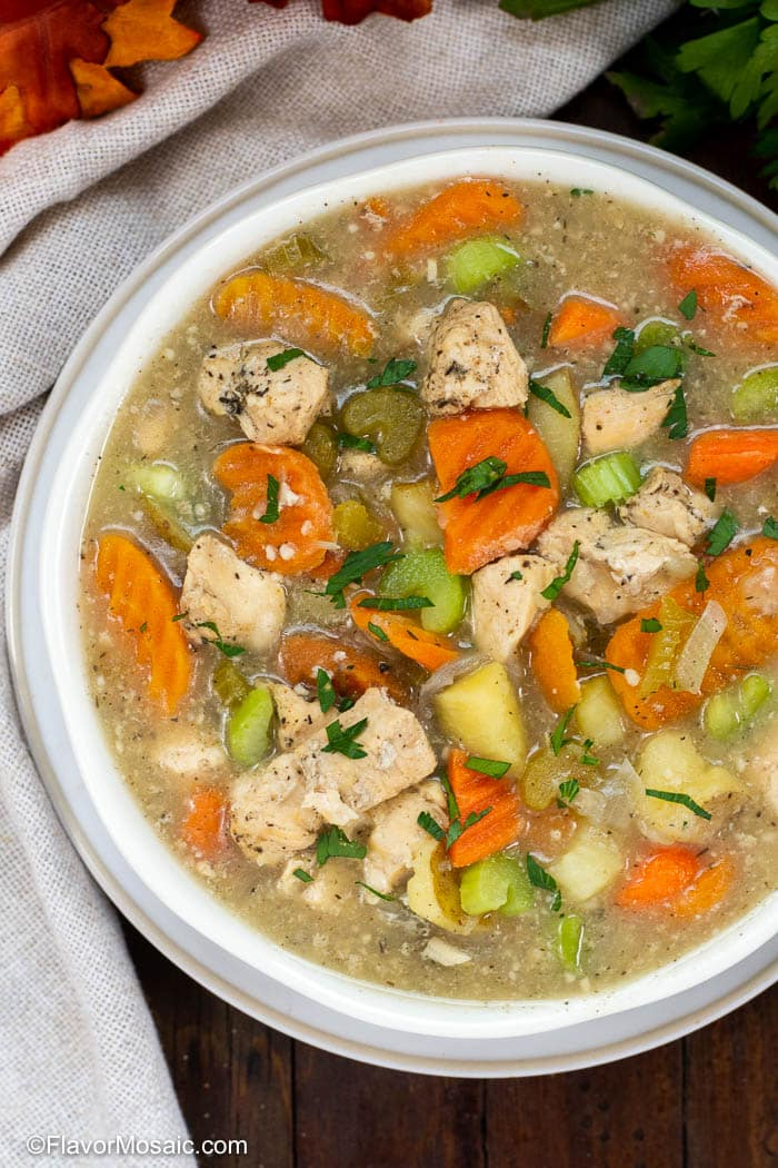 Overhead view of white bowl with Instant Pot Chicken Stew and a beige napkin on the side