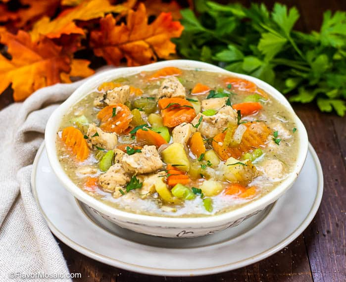 Horizontal photo of white bowl of Instant Pot Chicken Stew sitting on white plate with beige napkin and parsley and fall colored leaves in background.