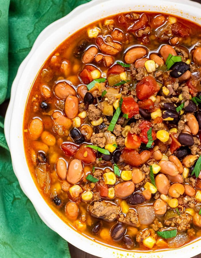 Overhead photo of Instant Pot Taco Soup in white bowl with green napkin beside it on dark wood background.