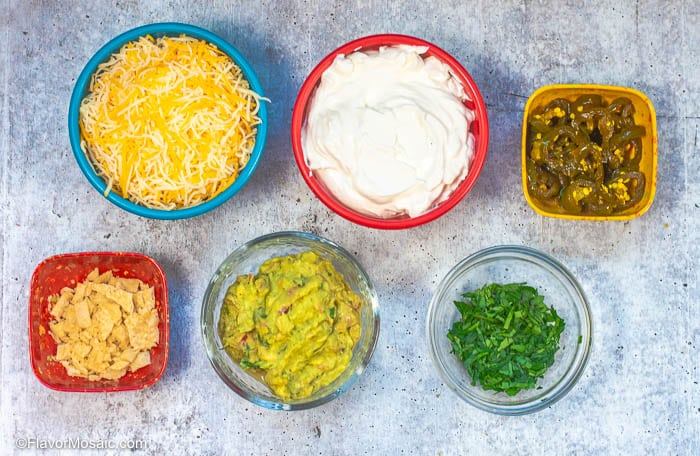 Overhead photo of taco toppings served in colorful small bowls, like a taco bar, with a blue gray granite background.
