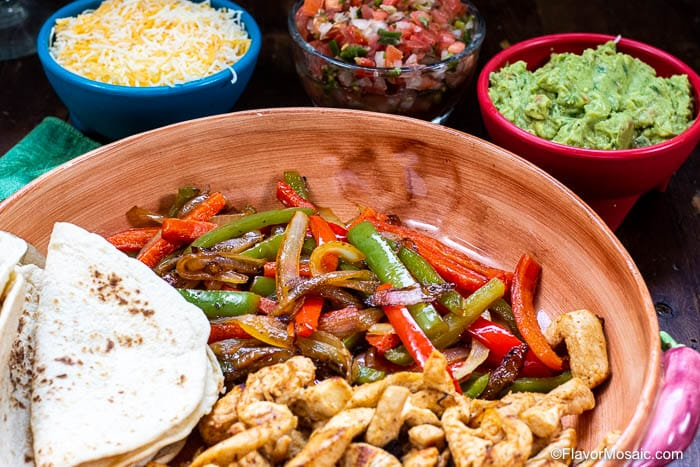 photo of fajita plate with fajita toppings in the background.