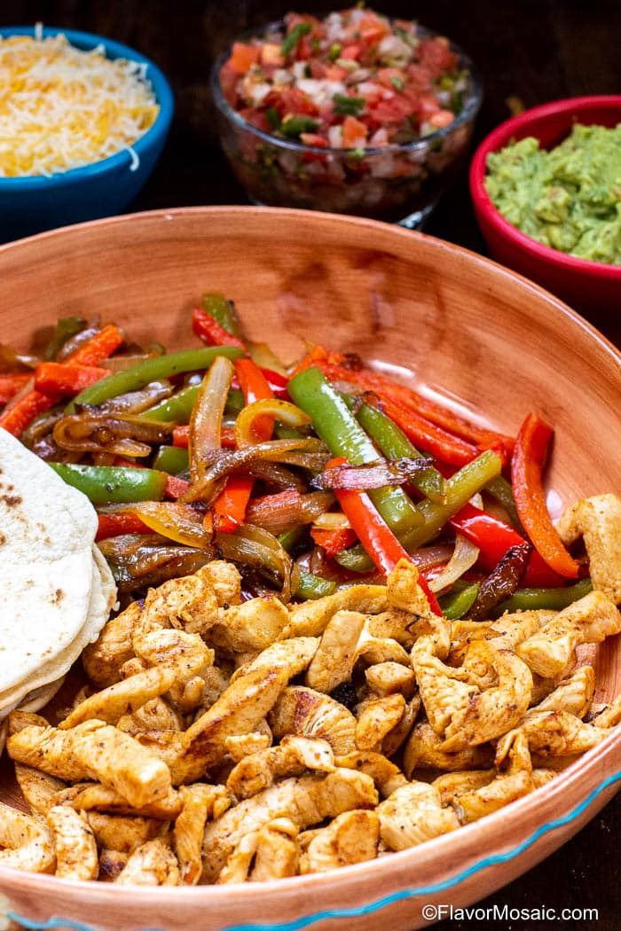 Platter with chicken fajita meat, flour tortillas, and sautéed onions, red and green bell peppers, with bowls of shredded cheese, pico de gallo and guacamole in the background.