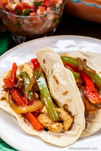 Two Chicken Fajitas with onions and red and green bell peppers in flour tortillas on white plate with a bowl of pico de gallo in the background.