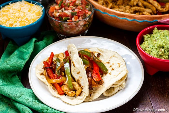 White plate with chicken fajitas surrounded by fajita toppings - shredded cheese, pico de gallo salsa, and guacamole.