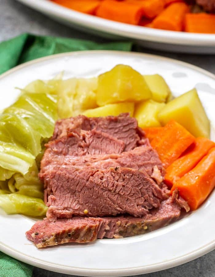 White plate with serving of corned beef with cabbage, carrots, and potatoes, with green napkin on the side and a partial view of serving platter in the background.