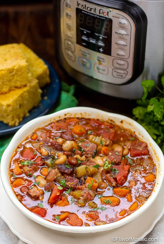 White bowl of Ham And Bean Soup with Instant Pot and plate of cornbread in the background.
