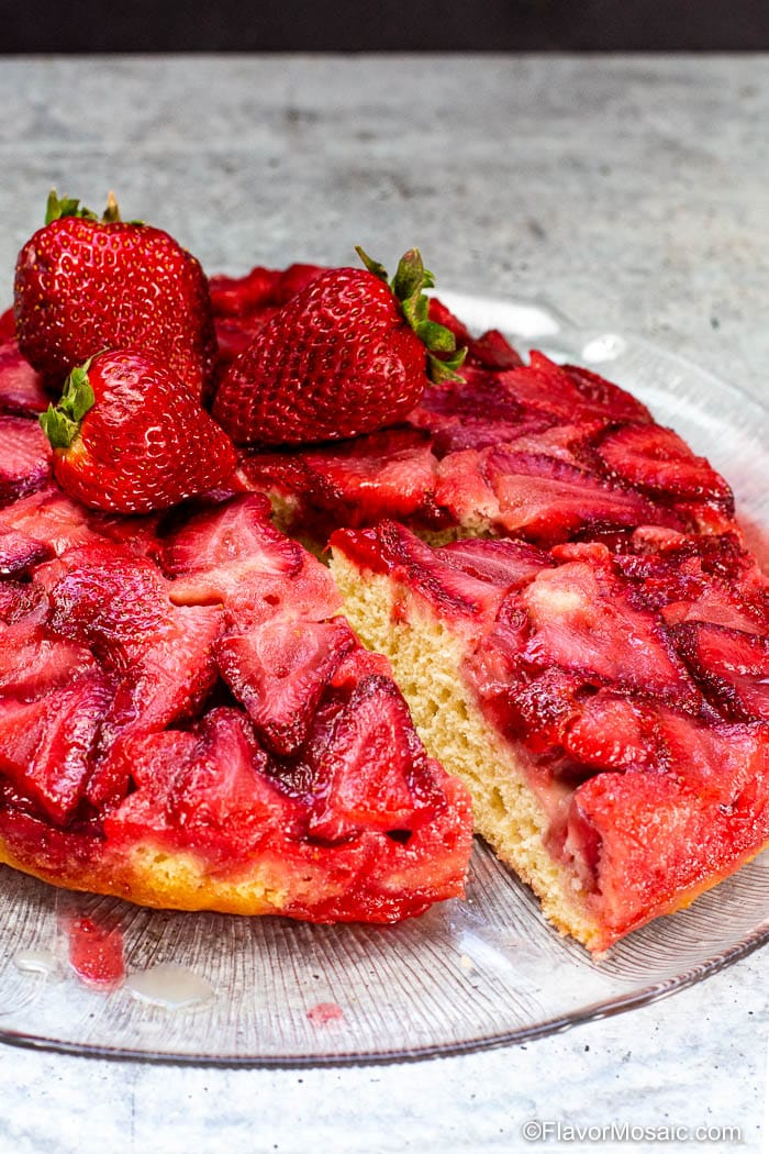 1 slice od Strawberry Upside Down Cake cut from the whole cake but sitting on the plate with the rest of the cake.