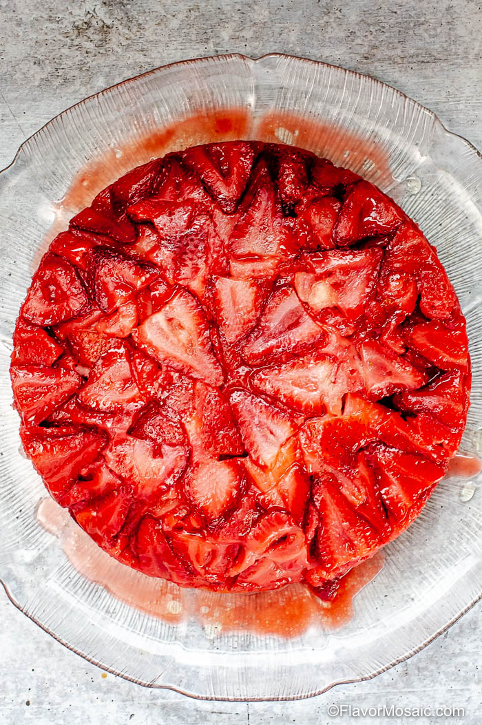 Overhead view of whole Strawberry Upside down Cake on a clear platter on a gray stone counter.