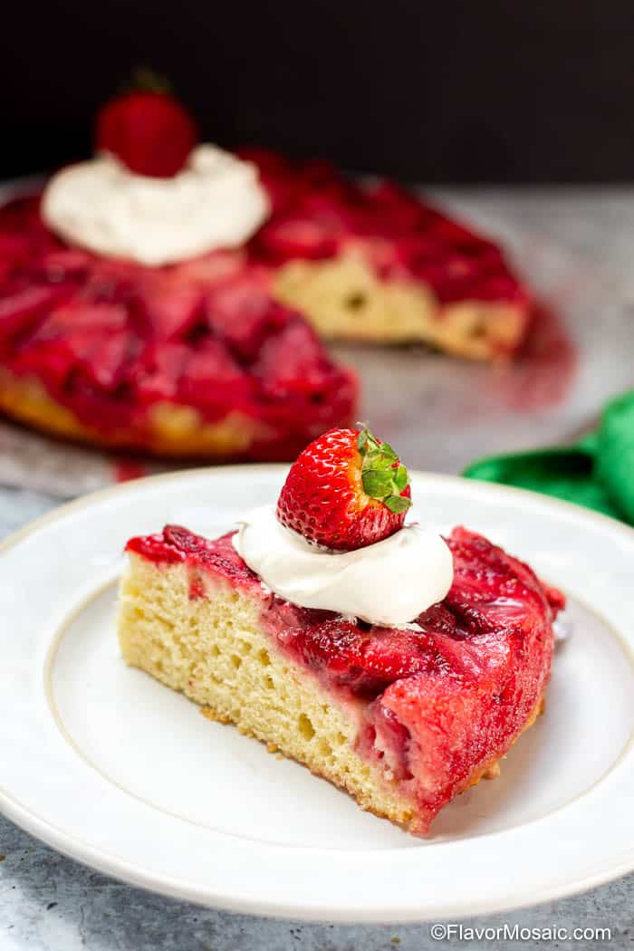 Single serving of Strawberry Upside Down Cake with whipped topping and strawberry and whole cake in the background.