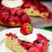 Single serving serving Strawberry Upside Down Cake on white plate topped with whipped cream and whole strawberry with whole cake in the background.