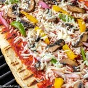 Grilled pizza with toppings on grill with red label with title in white text.