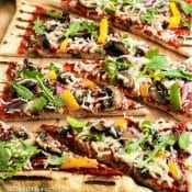 Slices of Grilled pizza with toppings on cutting board with red label with title in white text. 2
